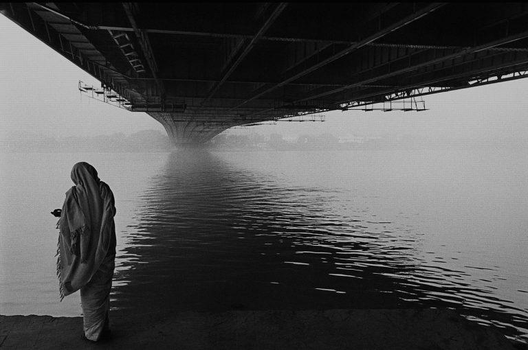 Woman standing under Howrah Bridge West Bengal offering prayers to river ganges